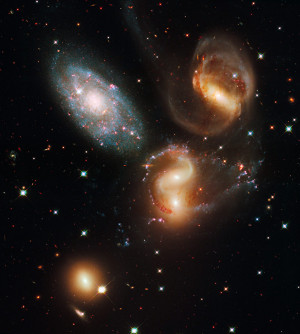 "This portrait of Stephan's Quintet, also known as Hickson Compact Group 92, was taken by the new Wide Field Camera 3 (WFC3) aboard NASA's Hubble Space Telescope. NGC 7319, at top right, is a barred spiral with distinct spiral arms that follow nearly 180 degrees back to the bar. Continuing clockwise, the next galaxy appears to have two cores, but it is actually two galaxies, NGC 7318A and NGC 7318B. NGC 7317, at bottom left, is a normal-looking elliptical galaxy that is less affected by the interactions. Sharply contrasting with these galaxies is the dwarf galaxy NGC 7320 at upper left. Bursts of star formation are occurring in the galaxy""s disk, as seen by the blue and pink dots."