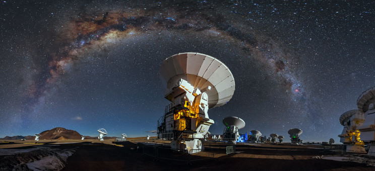 Like a celestial blanket the Milky Way forms an arc high above the antennas of the Atacama Large Millimeter/submilimeter Array. This arc is caused by the panoramic view of the image.