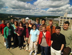 The Ask an Astronomer team, September 2007. Here are some of us on the roof of the Cornell Space Sciences Building, with Cayuga Lake in the background. From left to right: (back row) Anthony Milano, Ann Martin, Shannon Gutenkunst, Laura Spitler, Ryan Anderson, Pon Tangmatitham, Drew Brisbin, and Carl Ferkinhoff. (front row) Sabrina Stierwalt, Barbara Rojas, Briony Horgan, Betsey Adams, Rebecca Harbison, Kassie Martin-Wells, and Istvan Laszlo. (Credit: Brian Kent)