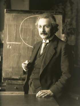 "Albert Einstein during a lecture in Vienna in 1921. Albert Einstein (1879 – 1955) was a German-born theoretical physicist and philosopher of science. He developed the general theory of relativity, one of the two pillars of modern physics (alongside quantum mechanics). He is best known in popular culture for his mass–energy equivalence formula E = mc2 (which has been dubbed ""the world's most famous equation""). He received the 1921 Nobel Prize in Physics ""for his services to theoretical physics, and especially for his discovery of the law of the photoelectric effect. The latter was pivotal in establishing quantum theory. (Credit: Ferdinand Schmutzer (1870–1928), restored by Adam Cuerden.)"