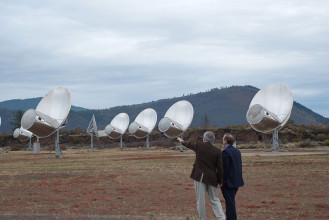 Front view of antennas of the Allen Telescope Array, a radio telescope for combined radio astronomy and SETI (search for extraterrestrial intelligence) research being built by the University of California at Berkeley, outside San Francisco. The first phase, consisting of 42 6-meter dish antennas shown here, was completed in 2007. Eventually it will have 350 antennas. This type of antenna is called an offset Gregorian design. The incoming radio waves are reflected by the large parabolic dish onto a secondary parabolic reflector in front of the dish, and then into a feed horn. A metal shroud along the bottom of the secondary reflector shields the antenna from ground noise. It covers the frequency range from 0.5 to 11.2 GHz. (Credit: Colby Gutierrez-Kraybill)